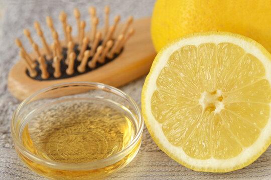 Apple cider vinegar and lemon with hair brush on grey towel - Homemade hair mask ingredients