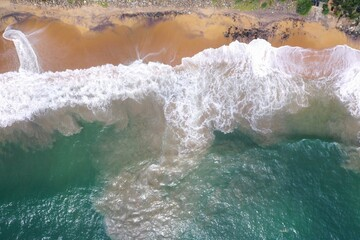 aerial drone bird view shot of the sea shore with turquoise blue water, large white waves and foam, empty beach with yellow sand, black rocks forming beautiful textures, patterns, shapes. Sri Lanka