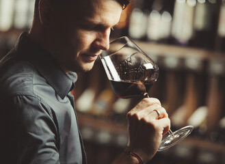 Sommelier smelling flavor of red wine in bokal on background of shelves with bottles in cellar. Male appreciating color, smell, quality and sediments of drink.