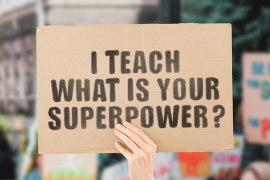 """The phrase """" I teach what is your superpower? """" on a banner in men's hand with blurred background. Social workers rights. Education. Job. Work. Security. Payment. School. University"""