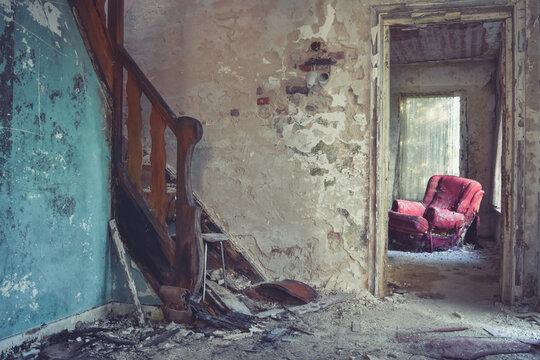 Hall d'entrée d'une vielle maison avec un escalier et un fauteuil rouge