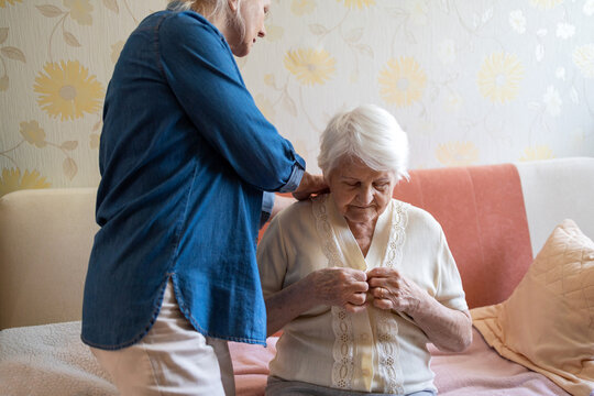 Woman helping senior woman dress in her bedroom