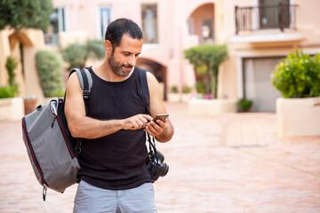 Ragazzo moro  canotta nera zaino in spalla e reflex sta in vacanza e manda un messaggio al cellulare nel centro del villaggio Fotomurales