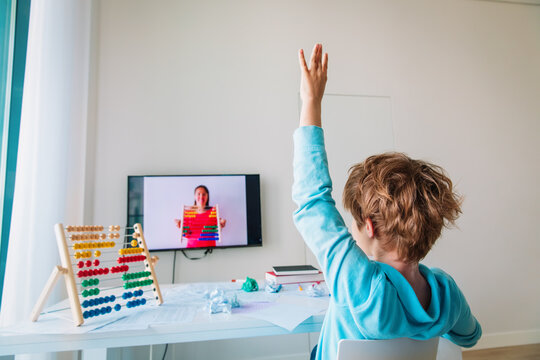kid learning at home, boy raising hand doing online math lesson