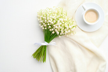 Papiers peints Muguet de mai Bouquet of flowers lily of the valley and morning coffee cup on white table. Breakfast for Mothers day or Womens day. Top view, flat lay.