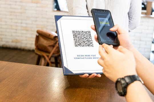Person scanning contactless menu QR code with smartphone as new normal. Code edited and not valid