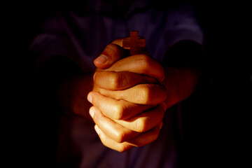Human hand holding the cross black background