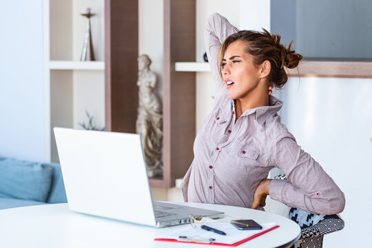 Portrait of young stressed woman sitting at home office desk in front of laptop, touching aching neck with pained expression, suffering from neck pain after working on pc