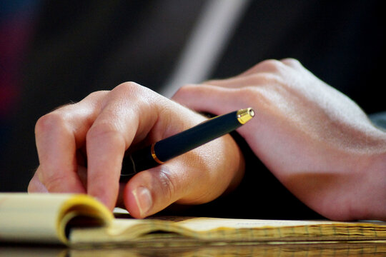 a business woman's hand with pen and notepad in a meeting