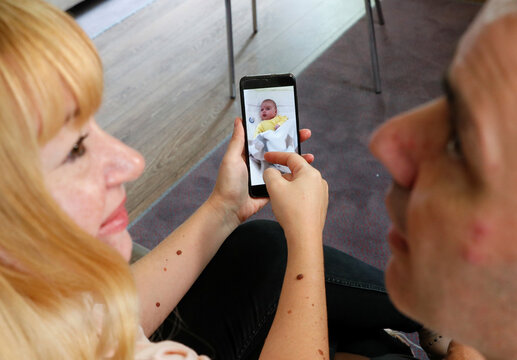 Jose Perez and Flavia Lavorino from Buenos Aires look at a picture of their son, in Kiev