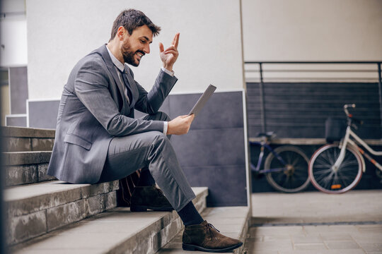 Young businessman sitting on the stairs outdoors after work and using tablet.