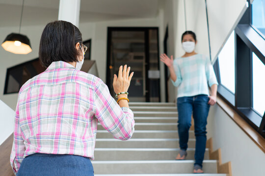 two asian woman are wearing face mask and making safe greeting during covid-19 or coronavirus outbreak to prevent infection. social distancing and new nomal lifestyle concept