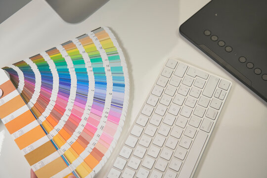 Woman freelance graphic designer at work in her home office chooses colors from palette for design and printing a new job. She work on a white desk with the black graphic tablet and computer keyboard.