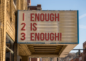 Door stickers Wall Decor With Your Own Photos Mockup of movie cinema billboard with message of Enough is enough on the marquee sign in downtown street