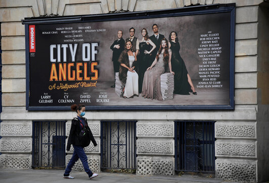 A woman wearing a protective face mask walks past a billboard outside of the Garrick Theatre promoting the West End musical 'City of Angels', following the outbreak of the coronavirus disease (COVID-19), in London, Britain