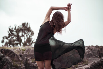 Woman in transparent dress with arms raised dancing against sky