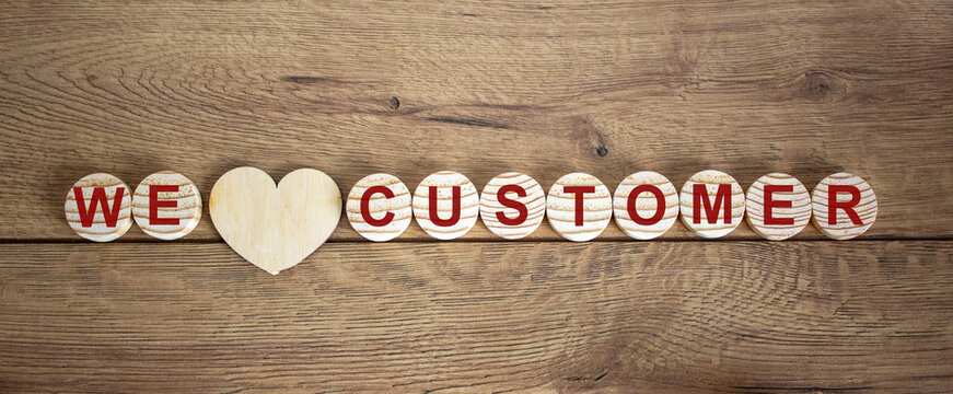 Wooden small circles with words 'we love customer' on wood background. Concept image.