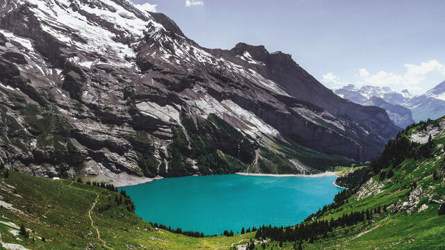 Aerial view of Oeschinensee Lake, Switzerland. Image features a tranquil and small lake filled with glacial water with the Swiss Alps in the background.