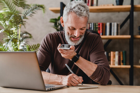 Senior man writing notes in notepad while talking by speakerphone from workspace
