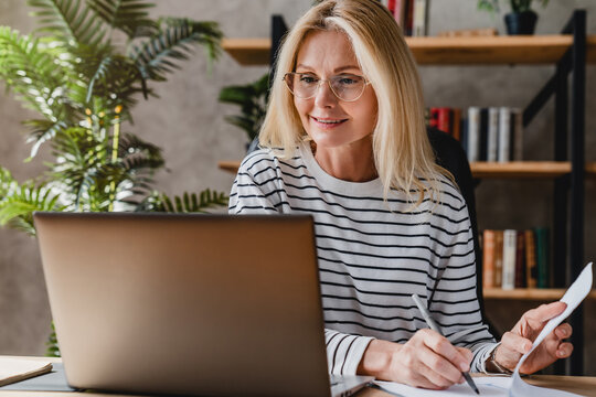 Senior stylish woman taking notes in notebook while using laptop at home office