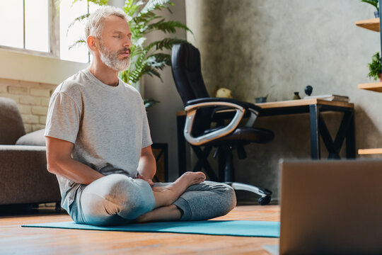 Middle aged sport man doing yoga and fitness at home using laptop