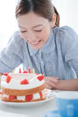 ケーキを笑顔で見つめる20代女性