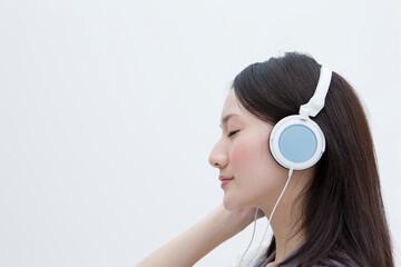 静かに音楽を聴く20代女性