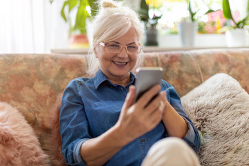 Senior woman using mobile phone at home