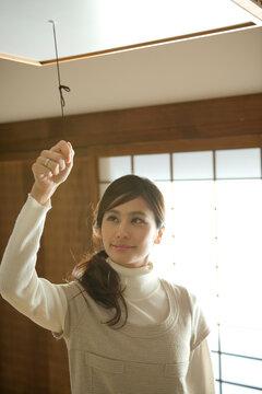 照明のスイッチを引く20代女性