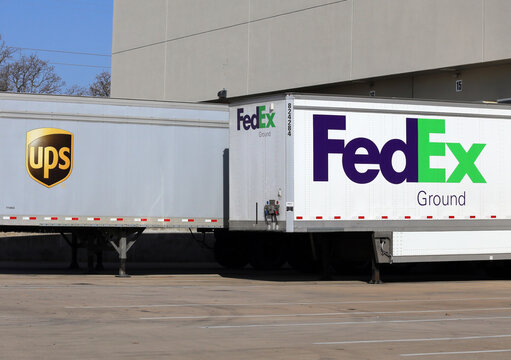 Grapevine, TX, USA - March 14, 2014: Fedex and UPS trailers parked next to each other at a loading dock. Fedex and UPS are two large multinational shipping companies.