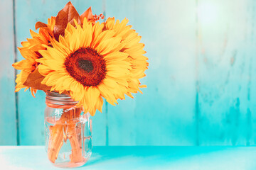 Tuinposter Zonnebloem Glowing sunflowers in a vase with turquoise background and copy space