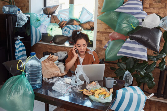 Unkempt young Asian woman having phone conversation at her cluttered flat