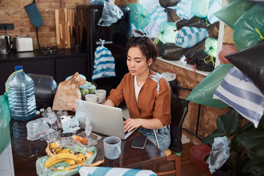 Concentrated woman working online in a messy flat