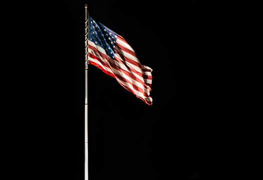 Pole with waving Old Glory American flag isolated on black, copy space