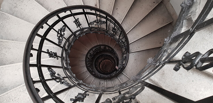 A spiral staircase spiraling down about five floors. The winding concrete stairs are empty. The metal hand rail is nicely decorated. The image approaches the golden ratio and Fibonacci spiral.