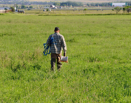 Rancher prepares to string new electric fence line around a pasture.