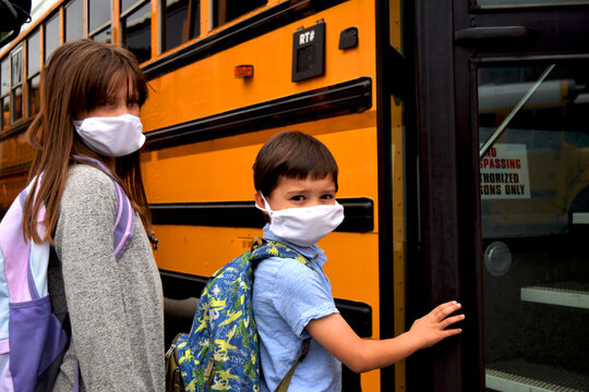 Children wearing face masks by school bus. A boy and girl wear facemasks while boarding a school bus. Education, back to school, school, medical, health, and safety concepts.