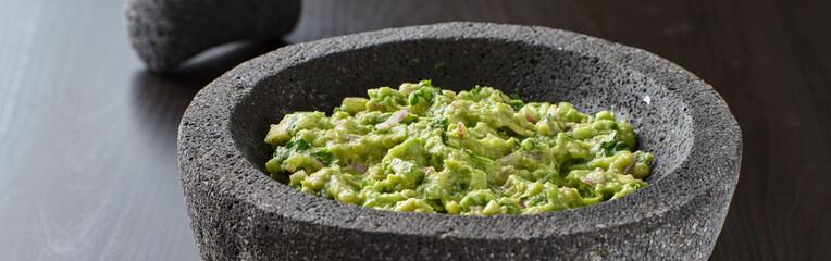 fresh guacamole in stone molajete panoramic composition