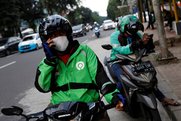 Online motorbike taxi drivers use their smartphones while waiting for customers in Jakarta