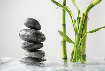 Stack of spa stones and bamboo in water against light background