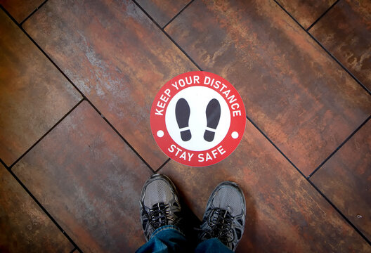 Floor sign on wood floor at business stating Social Distancing Stay Safe with shoes as graphic . A person's legs and shoes can be seen nearby