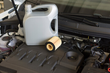 Engine oil and oil filter in the background of the engine compartment of a car