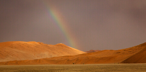 Rainbow shines over a sand dune in the desert in Namibia