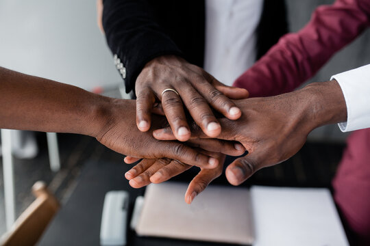 The hands of black people in the center hold each other to unite against racism in large countries. Black lives matter