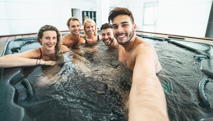 Happy friends taking selfie while doing jacuzzi in luxury house - Young people having fun together in hot tub - Youth millennial generation and wellness lifestyle holidays