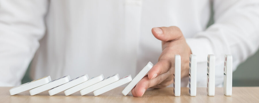 Business solution strategy with stoping domino effect concept for financial or investment protection and successful intervention with corporate person's hand blocking the collapse disruption.