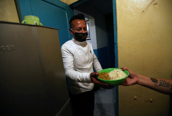 A tenant of a low-income boarding house receives a plate of food donated by El Chato and La Chicheria Demente restaurants, amidst the outbreak of the coronavirus disease (COVID19), in Bogota