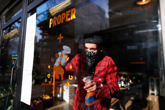 Argentine chef Leo Lanussol, owner of the Proper restaurant, cleans a window at the Gran Dabbang restaurant, in Buenos Aires