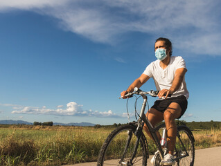 Young man on a bicycle on a country road wearing a mask