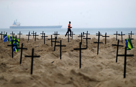 A man runs past the one hundred graves which were dug by activists of the NGO Rio de Paz on Copacabana beach symbolising the dead from the coronavirus disease (COVID-19), in Rio de Janeiro